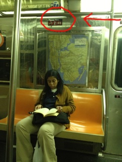 Subway sign above woman reading says please pray